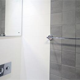 Image of a GRP shower pod with tiled feature wall fitted by Offsite Solutions.