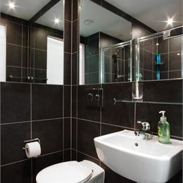 Corner View of Modern Black Tiled Bathroom Pod With Mirrors On Both Corners