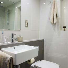 Corner View of Care Home Bathroom Pod, White Walls, Granite Effect Feature Wall Behind Toilet
