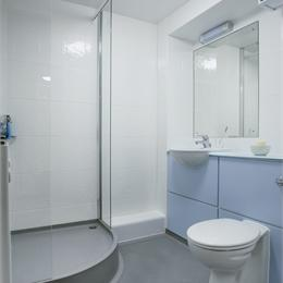Overview of military bathroom pod there's a corner round shower, white walls, a mirror