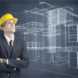 man in suit and hard hat looking up with a blueprint design in background