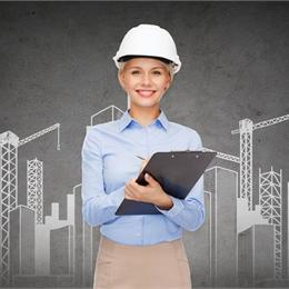 Smart dressed woman in blue shirt holding clipboard and wearing a hard hat
