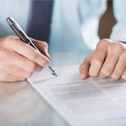 man signing a terms and conditions piece of paper
